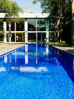 The swimming pool is lined in blue mosaic tiles and extends into the living room
