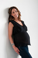 Smiling pregnant Caucasian woman, leaning against wall