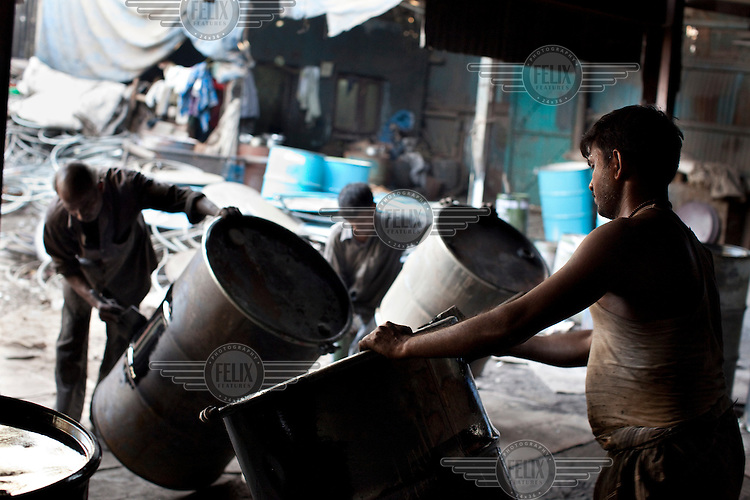 Men move large barrels at a recycling centre in Dharavi slum.