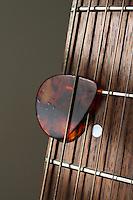 Pick (Plectrum) Under Strings on Guitar Fret Board