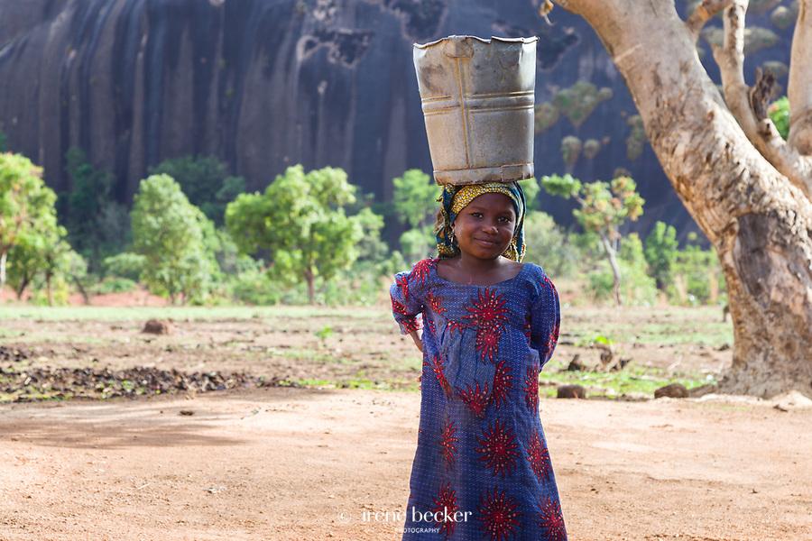 Fulani Girl carrying a bucket of water on her head in Kajuru, Kaduna State, Nigeria.