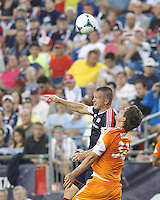 New England Revolution forward Chad Barrett (9) and Houston Dynamo defender Bobby Boswell (32) battle for head ball. In a Major League Soccer (MLS) match, Houston Dynamo (orange) defeated the New England Revolution (blue), 2-1, at Gillette Stadium on July 13, 2013.