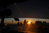 The road is crowded with cars and camels as Bedouins make their way to the Camel Beauty Contest near Abu Dhabi. Bringing their animals by truck or walking them for days, contestants from seven Arab countries set up camps for the week and compete.<br /> Camels are judged on their beauty by the size and shape of their necks, heads, humps, and toe cleavage.