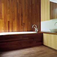 Several types of wood, both blonde and dark, are used in different ways on every surface of this bathroom