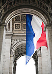 A French flag hangs from the Arc de Triomphe, Paris, France..