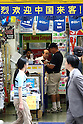 July 1, 2010 - Tokyo, Japan - Pedestrians walk past promotional signs written in Chinese displayed at an electronics store in Akihabara district, Tokyo, Japan, on July 1, 2010. On Tursday, Japan will significantly relax visa requirements for Chinese citizens to attract an increasing number of big-spending Chinese tourists to boost its economy. Japanese Foreign Minister Katsuya Okada told a press conference earlier that the number of households eligible to visit will increase 10-fold to 16 million a year.