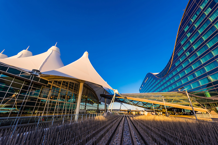 The Westin Denver International Aiport Hotel (on right) and Jeppesen Terminal (on left). The design of the hotel resembles a bird in flight and the curved roof mimics the concave shape of the terminal's tent like roof.