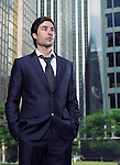 Portrait of a young businessman in a suit standing in city downtown with office buildings in the background. Toronto, Canada.