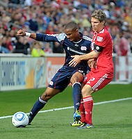 New England defender Darrius Barnes (25) shields the ball from Chicago midfielder Logan Pause (12).  The Chicago Fire defeated the New England Revolution 3-2 at Toyota Park in Bridgeview, IL on Sept. 25, 2011.
