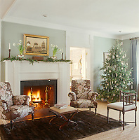 A pair of comfortable armchairs covered in pretty brown chintz is arranged on either side of a blazing log fire in the living room which is decorated for Christmas with a traditional tree