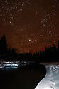 The constellation Orion and the Yaak River at night in winter. Yaak Valley, Montana.