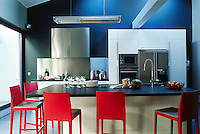 Black granite work surfaces, stainless steel cupboards and bright red chairs have been combined to stunning effect in the large and spacious kitchen