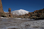 Snow capped Mount Teide with ice covered puddle in the foreground, Tenerife, Canary Islands.