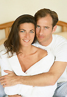 Couple Together On A Bed Looking At Camera