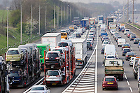 Car transporter lorries travelling among congested traffic on M1 motorway in Hertfordshire, United Kingdom