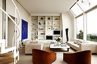 At one end of the contemporary living room are open bookshelves designed by Christian Liaigre