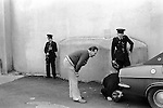 RUC, Royal Ulster Constabulary check under car for a bomb. car owner looks on.  Derry Londonderry Northern Ireland 1979