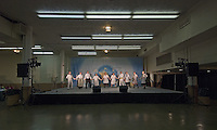 Dancers perform on a lighted stage in a nearly empty basement hall at the International Festival in Columbus, Ohio.<br />