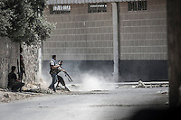 Free Army rebels fire with Kalashnikovs as they repel an offensive attack by Assad's army during a battle in the neighborhood of Jaser Al Nerab. Intensive combats have taken place in the area under control of the rebels close to the airport to regain the position lost by the Assad's troops.