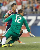 New England Revolution midfielder Diego Fagundez (14) watches shot get cleared off the line. Toronto FC goalkeeper Joe Bendik (12). In a Major League Soccer (MLS) match, Toronto FC (white/red) defeated the New England Revolution (blue), 1-0, at Gillette Stadium on August 4, 2013.