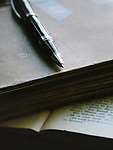 An old black pen laid on vintage books, with a printd page at the bottom.