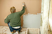Plastering student working on a plasterboard wall, Able Skills, Dartford, Kent.