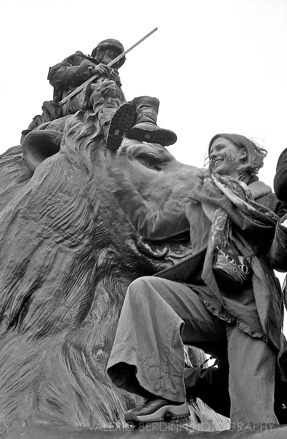 Trafalgar Square. People climb the bronze lions at the Stop The War demonstration. London, 15/02/2003