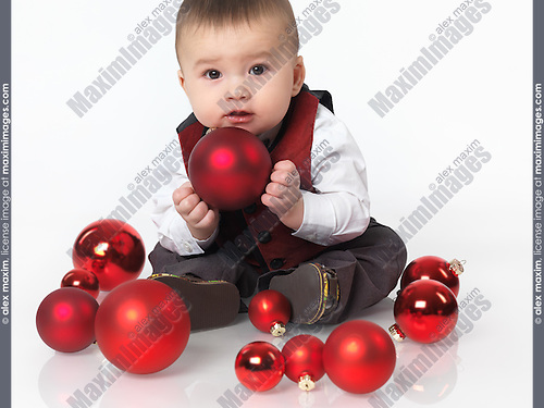 Six month old baby boy sitting with a red bauble Christmas decoration in his hands. Isolated on white background.