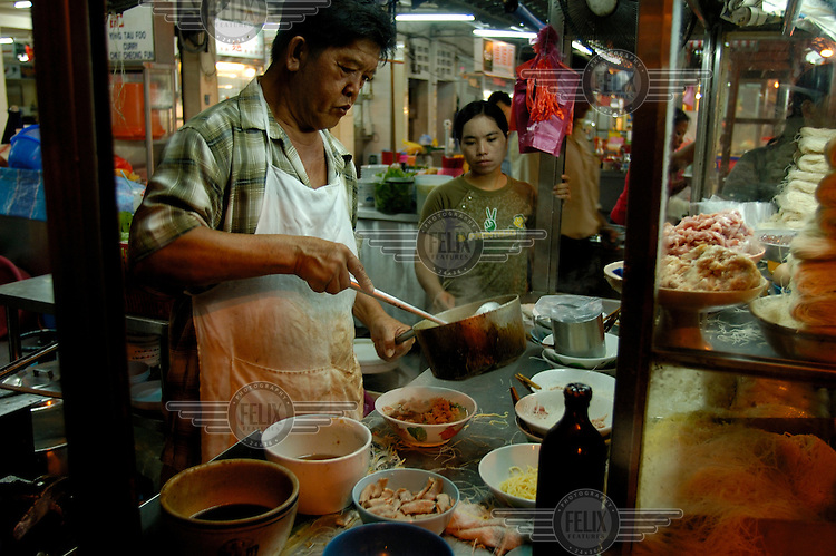 Cook at a Chinese food stall (pork liver noodles stall) at a mostly Chinese night food market on Jalan Alor in the Golden Triangle.