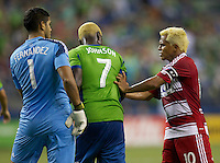 David Ferreira, right, of FC Dallas pushes Eddie Johnson of Seattle Sounders FC while Raul Fernandez watches during play at CenturyLink Field in Seattle Saturday August, 3, 2013. The Sounders defeated Dallas 3-0.