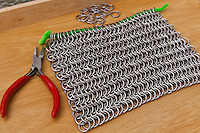 A sheet of European 6 in 1 chain mail in the front, a pair of chain mail pliers on the side, and rings ready to be attached in the background.