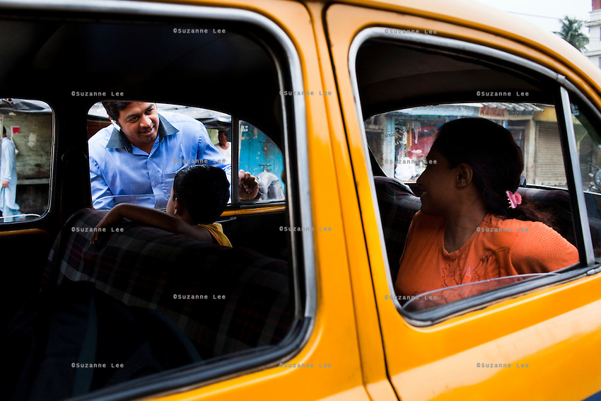 Razia Shabnam (in orange) says farewell to her husband as she leaves in a taxi with her son Saihaan, to referee an all-India invitational boxing competition in the neighbouring town of Burnpur, Calcutta, West Bengal, India. Razia Shabnam, 28, was one of the first women boxers in Kolkata. She was also the first woman in her community to go to college. She is now a coach and one of only three international female boxing referees in India. Photo by Suzanne Lee for Panos London