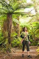 Young woman in rainforest under tree fern on forest walk near Haast, South Westland, UNESCO World Heritage Area, West Coast, New Zealand, NZ