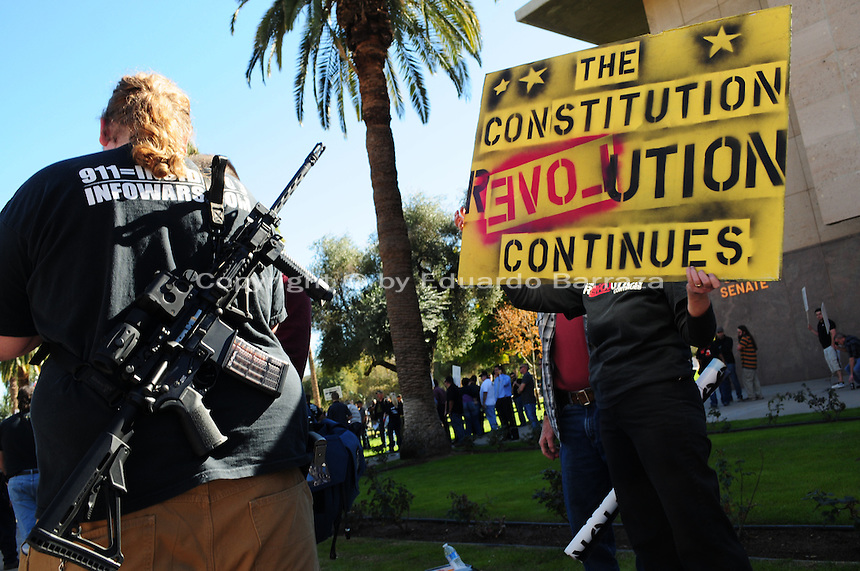 "Phoenix, Arizona. January 19, 2013 - A demonstrator carries an automated weapon on his back next to another protester holding a sign during Saturday's rally in Phoenix. Gun owners mobilized Saturday to oppose possible changes to guns and ammunition availability. As President Barack Obama proposed new gun regulations last week, gun owners demonstrated against it with national ""Guns Across America"" rallies to defend the Second Amendment. Dozens showed up at the Arizona State Capitol, many of them carrying weapons. Photo by Eduardo Barraza © 2013"