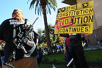 """Phoenix, Arizona. January 19, 2013 - A demonstrator carries an automated weapon on his back next to another protester holding a sign during Saturday's rally in Phoenix. Gun owners mobilized Saturday to oppose possible changes to guns and ammunition availability. As President Barack Obama proposed new gun regulations last week, gun owners demonstrated against it with national """"Guns Across America"""" rallies to defend the Second Amendment. Dozens showed up at the Arizona State Capitol, many of them carrying weapons. Photo by Eduardo Barraza © 2013"""