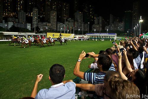 Spectators watch a race at the Hong Kong Jockey Club's Happy Valley racecourse.