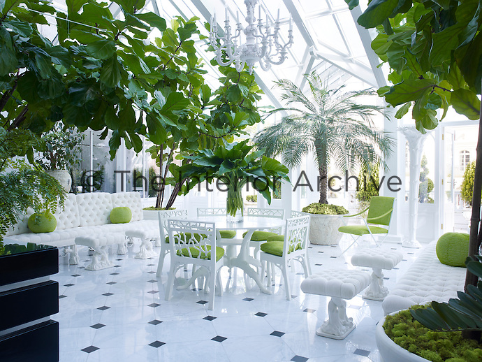 Ann Getty designed the table and seating in the conservatory, their light green cushions matching the lush leafy trees