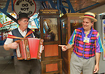Brooklyn, New York, USA. 10th August 2013. BOB YORBURG, AKA Professor Phineas FeelGood the Magician, of Yorktown Heights, points to BOB STUHMER, a fellow AMICA member playing the automatic accordian. Behind them is Grandmothers Predictions, the famous fortune telling game, during the 3rd Annual Coney Island History Day celebration. Yorburg restored Coney Island's Grandma after the game was seriously damaged during Hurricane Sandy in October 2012.
