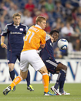 New England Revolution forward Kenny Mansally (7) attempts to control the ball as Houston Dynamo defender Andre Hainault (31) defends. In a Major League Soccer (MLS) match, the New England Revolution tied Houston Dynamo, 1-1, at Gillette Stadium on August 17, 2011.