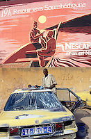 Senegal. Dakar. Sombedioune district (neighborhood).                                                          Car repair shop. On the wall, a painting shows on the atlantic ocean the fishermen' return in the evening  with their boats and with new fresh fishes . Every day, a fish market takes place in Sombedioune on the beach.                                                                                    This drawing is an advertising for the nestle product, the nescafe.  © 2000 Didier Ruef