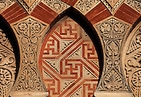 Architectural detail of the Puerta de San Ildefonso, built under Al-Hakam II in the 10th century, one of the West facade entrances to the Cathedral-Great Mosque of Cordoba, on the Calle Torrijos in Cordoba, Andalusia, Southern Spain. This detail shows the intricately carved vegetal patterns, mosaic work and red brick on an overlapping arch design. The first church built here by the Visigoths in the 7th century was split in half by the Moors, becoming half church, half mosque. In 784, the Great Mosque of Cordoba was begun in its place and developed over 200 years, but in 1236 it was converted into a catholic church, with a Renaissance cathedral nave built in the 16th century. The historic centre of Cordoba is listed as a UNESCO World Heritage Site. Picture by Manuel Cohen