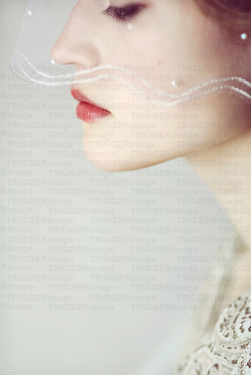 Close portrait of young woman looking down to the side with a bridal veil covering parts of her face
