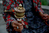 A lady spins a prayer wheel. Bhutan is a Buddhist country.  Arindam Mukherjee..