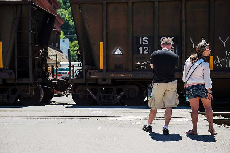 UNITED STATES - JULY 5: The beauty queen for the West Virginia Freedom Festival car show waits for a train loaded with coal to rumble through downtown Logan, W. Va., on July 5, 2014, as she makes her way from the car show to the main festival area. (Photo By Bill Clark/CQ Roll Call)