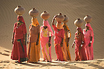Women bear the responsibility of fetching water from the sparse wells within Rajasthan's vast Thar Desert. Trekking up the side of a sand dune, women expertly balance large clay water vessels atop their heads.
