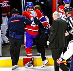 10 February 2010: With blood dripping from under his helmet, Montreal Canadiens' defenseman Josh Gorges is helped off the ice by trainers, followed by the team physician after blocking a slapshot during a game against the Washington Capitals at the Bell Centre in Montreal, Quebec, Canada. The Canadiens defeated the Capitals 6-5 in sudden death overtime, ending Washington's team-record winning streak at 14 games. Mandatory Credit: Ed Wolfstein Photo