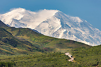 Tour bus travels the park road as Mount McKinley, north America's largest peak looms in the distance. Denali National Park, interior, Alaska.