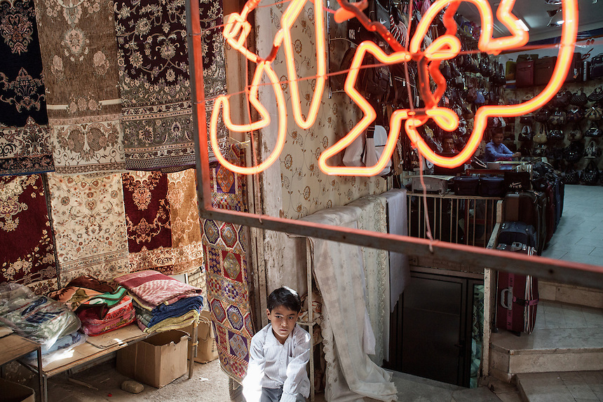 A boy with persian rug hanging in the background at Yazd Bazaar. Yazd, which located in the middle of desert of Central Iran, is one of the oldest living city in the world. Yazd was visited by Marco Polo in 1272, who described it as a good and noble city and remarked its silk production. The name Yazd means worship. And badgir is one of distinctive feature of this city.