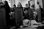 "Amber Blankenship, 5, takes a peek at Wooster, guidedog for Maggee (cq Maggee) Jespersen, second from left, who prayed with others on Ash Wednesday, Feb. 25, 2009, at Cathedral of the Sacred Heart in Raleigh.  Jespersen, who has lost most of her eyesight due to retinitis pigmentosa, says of Wooster, ""My faith is totally turned over to him, and I lean on him every day.  I feel safe and secure when he's leading me.""  Jespersen was sad because her yellow lab, age 9, is about to retire, and she'll have to find a new dog.  ""He's just getting tired,"" she said.  Seeing Wooster age, and dealing with an accelerated loss of her eyesight over the past 6 months, are challenges that Jespersen believes have a purpose.  ""Everything is a lesson from God,"" she said. ""These challenges are helping me get to a better place.""  Staff photo by Ted Richardson/The News & Observer"