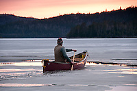 Solo paddling a canoe at dusk on a frozen Smoothwater Lake during an early spring trip to Lady Evelyn-Smoothwater Provincial Park in Ontario Canada.